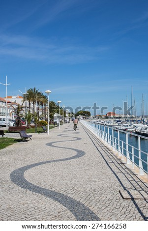 VILA REAL SANTO ANTONIO, PORTUGAL - APRIL 29 2015. A cyclist enjoys this promenade patterned with curves along the banks of the Guadiana river in this Algarve town of Vila Real de Santo Antonio.