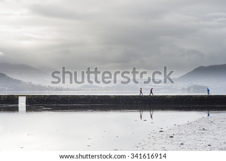 VILABOA, SPAIN - FEBRUARY 15, 2015: Some people walk over a stone walkway above the sea, on an inlet of the Ria de Vigo. - stock photo