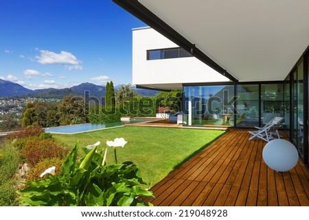 Villa, infinity swimming pool in the garden - stock photo
