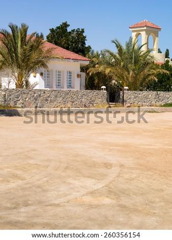 Villa on a sand beach with palms on the tropical island. - stock photo