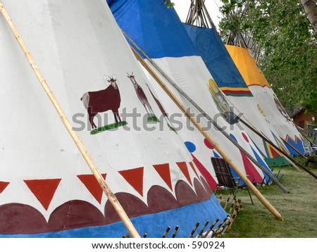 Village during Calgary Stampede. CalgarJuxtoposition of traditional tepees and modern lawn chairs at Indian y, Alberta, Canada. - stock photo