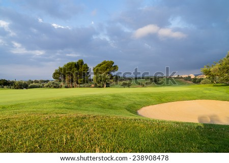 Village Golf Panoramica, the sun shining over a golf course lined with buildings and trees - stock photo