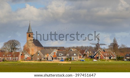 Village of Burdaard with church an historic windmill on Frisian countryside. Just North of Leeuwarden, Friesland.