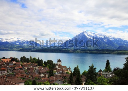 Village of Oberhofen with lake of Thun and snowy mountains, Switzerland