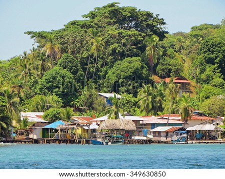 Village of Old Bank on the coast of the Caribbean sea with lush tropical vegetation in background, Bastimentos island, Bocas del Toro, Panama - stock photo