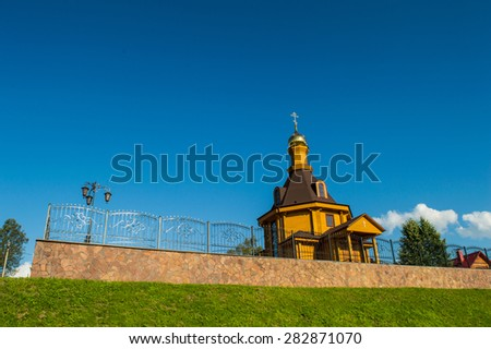 Village russian orthodox church with glided cupola on deep blue sky background - stock photo