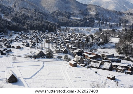 Village with thatched roof houses covered in snow  - stock photo