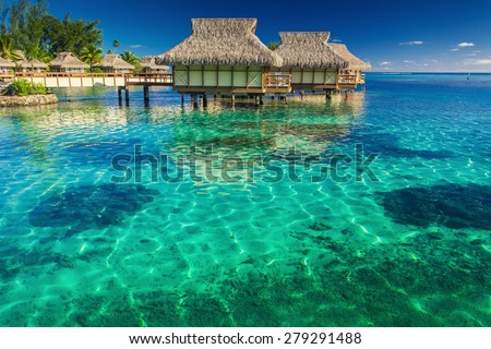 Villas in the lagoon with steps into shallow clean water with coral - stock photo