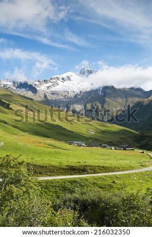 VILLE DES GLACIERS, FRANCE - AUGUST 27: Small village with Glacier Needles in the background. The region is a stage at the popular Mont Blanc tour. August 27, 2014 in Ville des Glaciers. - stock photo