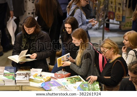 VILNIUS - FEBRUARY 26: Many people choose books at the indoor book market on February 26, 2016 in Vilnius, Lithuania. Vilnius is the capital of Lithuania and its largest city. - stock photo