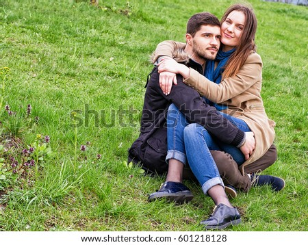 Vilnius, Lithuania - April 23, 2016: Young girl sitting on boys lap in the spring green grass