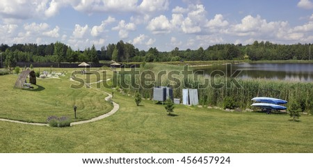 VILNIUS, LITHUANIA - JULY 02, 2016: Area of summer holiday and rest  with  grass beach, kayak, umbrellas and  cabins for disguise near the lake on Lavender Village in Kiemeliu rural area.