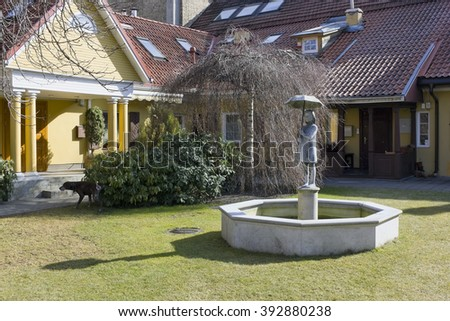 VILNIUS, LITHUANIA - MARCH 13, 2016: Fountain with girl's sculpture with an umbrella in the yard of the wooden house on Tilto (Bridge) Street . The sculptor of Romas Kvintas lives in the same house - stock photo