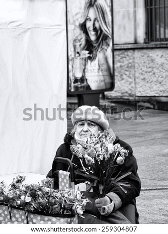 VILNIUS, LITHUANIA - MARCH 7: woman selling flowers in annual traditional crafts fair - Kaziuko fair on Mar 7, 2015 in Vilnius, Lithuania. Woman selling flowers in the street. Black and white photo