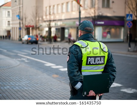 VILNIUS - OCT 28: Police Officer on patrol in Gediminas Avenue on October 28, 2013 in Vilnius, Lithuania. Gediminas Avenue is the main street in Vilnius centre. It is popular for shopping and dining.