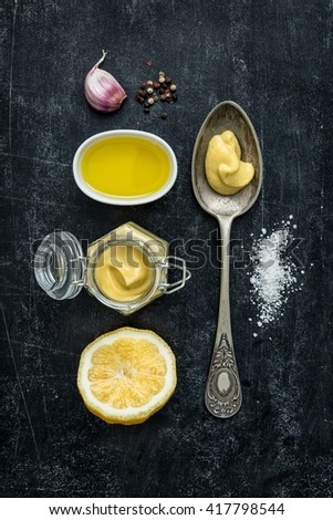 Vinaigrette dressing - recipe ingredients on black chalkboard background. Lemon, olive oil, mustard, garlic, salt and pepper. Flat lay composition (from above, top view). - stock photo