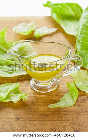 Vinaigrette (emulsion of vinegar with olive oil) in a glass gravy boat with iceberg lettuce leaves on a wooden table with white background, vertical