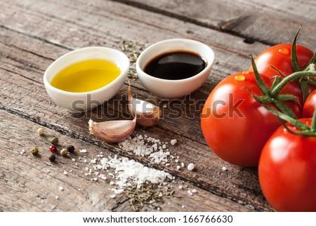 Vinaigrette or french dressing recipe ingredients on vintage wood background. Olive oil, balsamic vinegar, garlic, salt and pepper. - stock photo