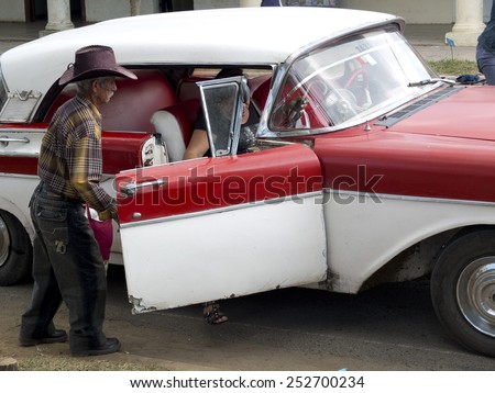 VINALES, CUBA - DECEMBER 16:  An old gaucho wearing a leather hat is opening the door of an american vintage car,on december 16, 2014, in Vinales, Cuba  - stock photo