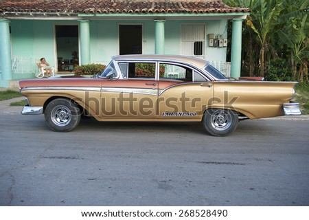VINALES, CUBA - MAY, 2011: Classic American car sits on a quiet street in front of a traditional Cuban house.
