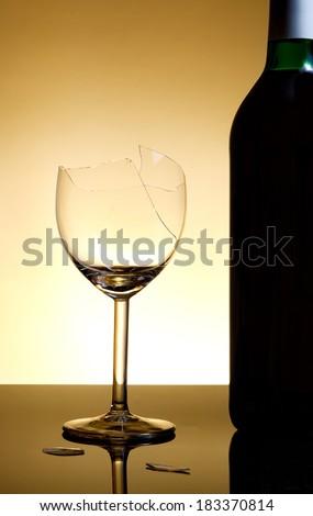 Vine bottle and broken glass on orange background - stock photo