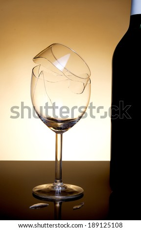 Vine bottle and broken glass on orange background - stock photo
