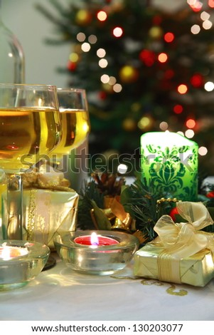 Vine, candles and gifts on background with blurred lights.