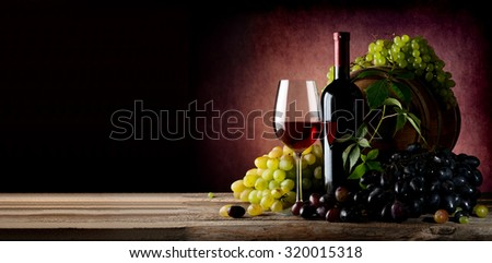 Vine of grape with wine on wooden table - stock photo