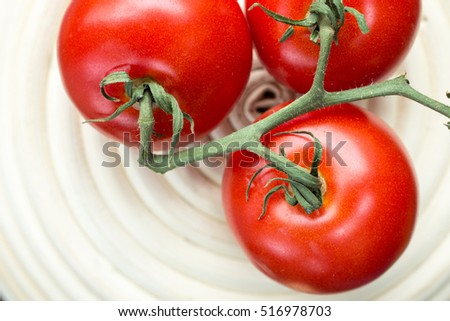 Vine ripe red tomatoes over a white bowl.