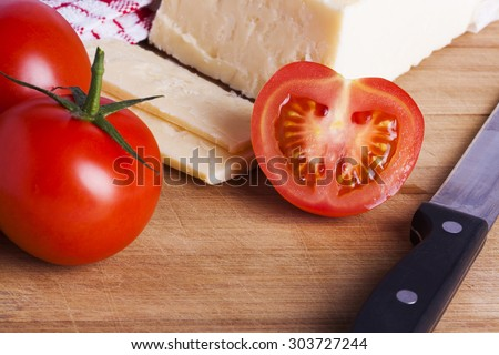 Vine tomatoes and cheddar cheese with knife on wooden board for picnics and healthy eating