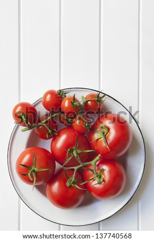Vine tomatoes in rustic enamel bowl over white timber.  Lots of copy space. - stock photo