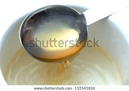 Vinegar being poured onto a measuring spoon