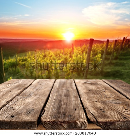 vineyard at sunset in the Chianti region in Italy and brown table  - stock photo