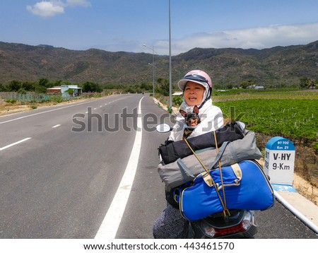 Vinh Hy town, Ninh Thuan province, VietNam - March 26, 2016 : woman resting with pet dog chihuahua after a long trip picnic by motorcycle
