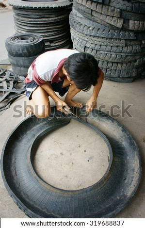 VINH LONG, VIET NAM- JULY 27: Vietnamese worker working at Mekong Delta trade village to recycle tire, man cut out rubber from tyre, Vinhlong, Vietnam, July 27, 2015