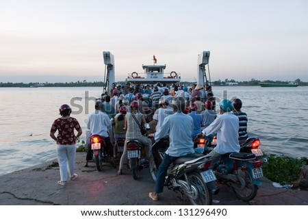 VINH LONG, VIETNAM - MARCH 6: Crowd of biker try to access a ferry across Mekong river on March 6, 2009 in Vinh Long. Mekong river runs from the Tibetan Plateau through six Asian countries.
