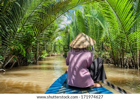 VINH LONG, VIETNAM - MARCH 6: Vietnamese woman paddling a traditional boat in the Mekong delta on March 6, 2009 near Vinh Long. The Mekong river is a major route for transportation in Southeast Asia.