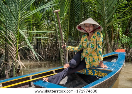 VINH LONG, VIETNAM - MARCH 6: Vietnamese woman posing in a traditional boat in the Mekong delta on March 6, 2009 near Vinh Long. The Mekong river is a major route for transportation in Southeast Asia.