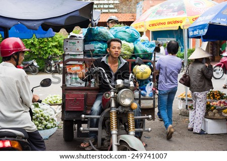 Vinh Long, Vietnam - Nov 30, 2014: Motorbike driver transporting fruits at Vinh Long market, Mekong delta. Transportation by motorbike is the fast, flexible and cheap way in Mekong delta