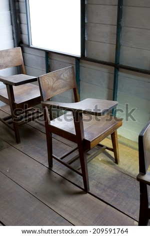 Vintage a school chair with a fold-up tablet/desk made from wood. - stock photo