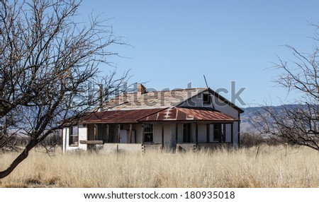 Vintage abandoned farm house with corrugated metal roof, stands in dry grass and weeds in semi-desert countryside landscape - stock photo