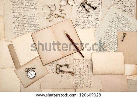 vintage accessories and open book over old letters and cards. nostalgic background - stock photo