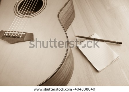 vintage acoustic guitar and notebook pencil