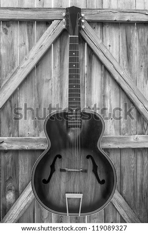 Vintage acoustic guitar hanging on an old, crooked, weather-beaten fence, monochrome.
