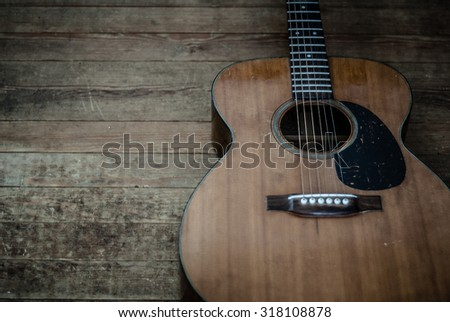 Vintage acoustic guitar on a distressed wood floor.