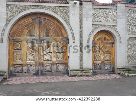 Vintage aged brown old wooden gate in brick wall. - stock photo