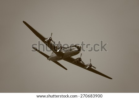 Vintage Aircraft in the Air with four propeller engines - stock photo