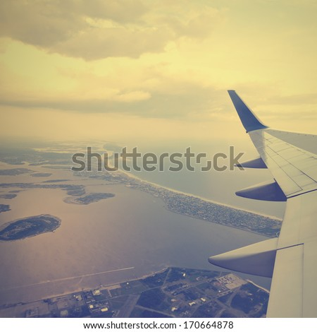 VIntage aircraft wing with aerial view of landscape and sky with the clouds - stock photo