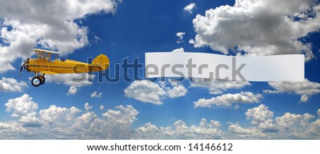 Vintage airplane pulling blank sign over bright sky