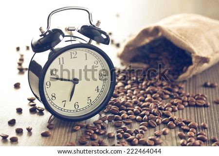 vintage alarm clock and coffee beans on wooden table - stock photo
